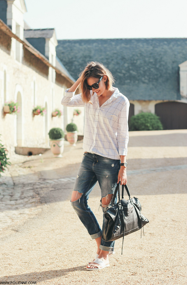 Paulien is wearing a chequered shirt from Women'Secret, ripped jeans from Zara, slides from Michael Kors, bag from Balenciaga and Sunglasses from Celine