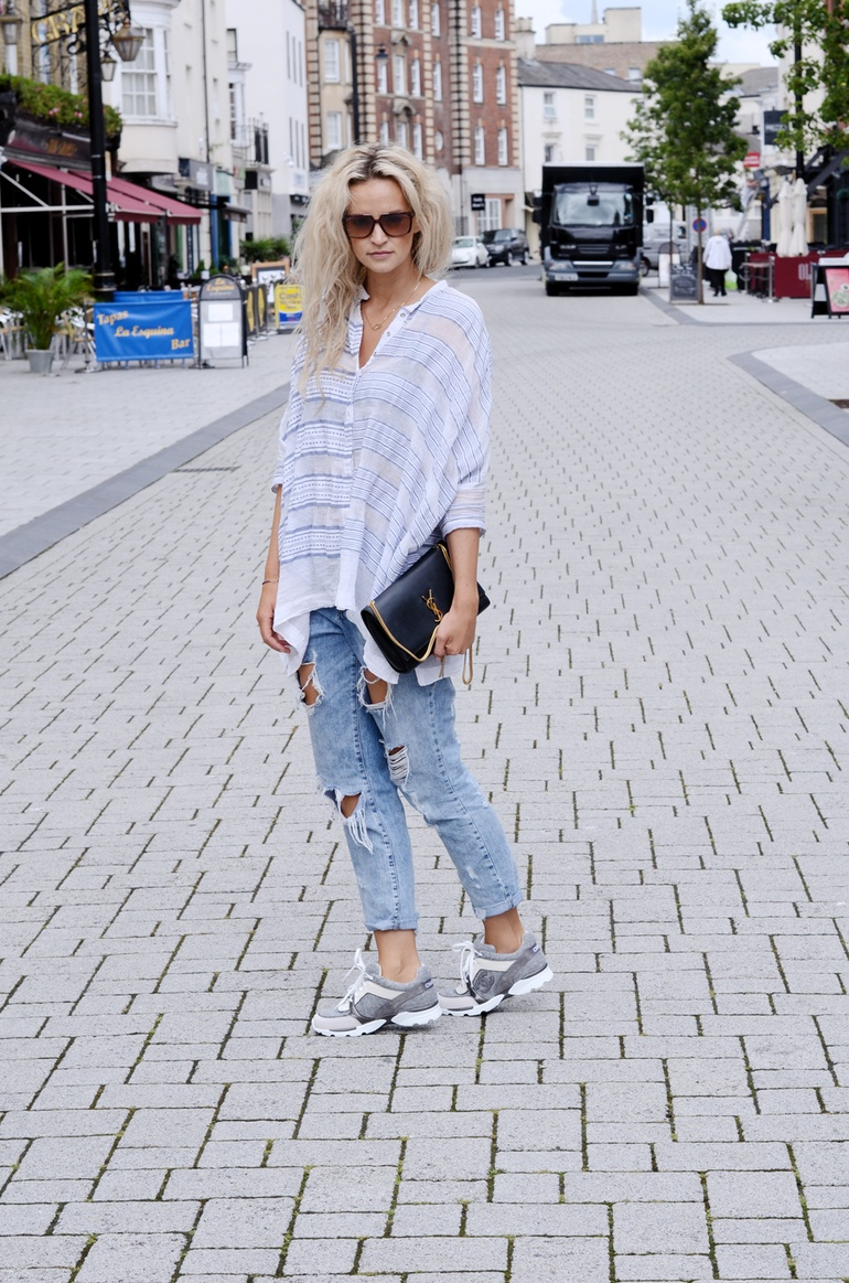 Anouk Yve is wearing a oversized shirt from LemLem, ripped jeans from Zara, sneakers from Chanel, and bag from Laurent