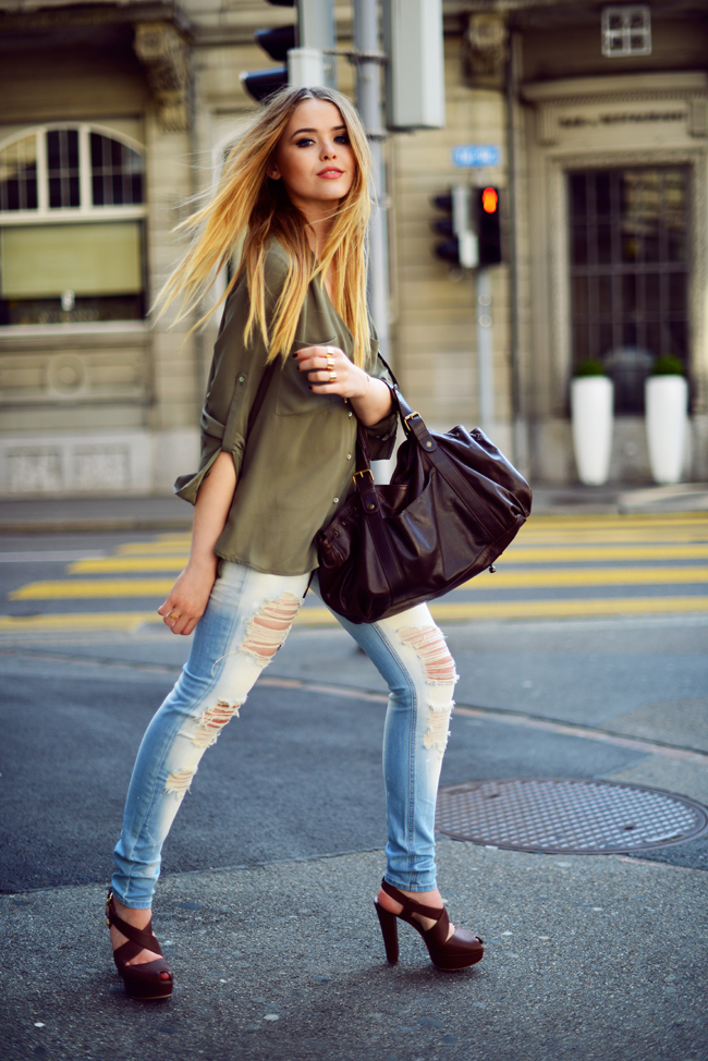Kristina Bazan in olive shirt and ripped jeans