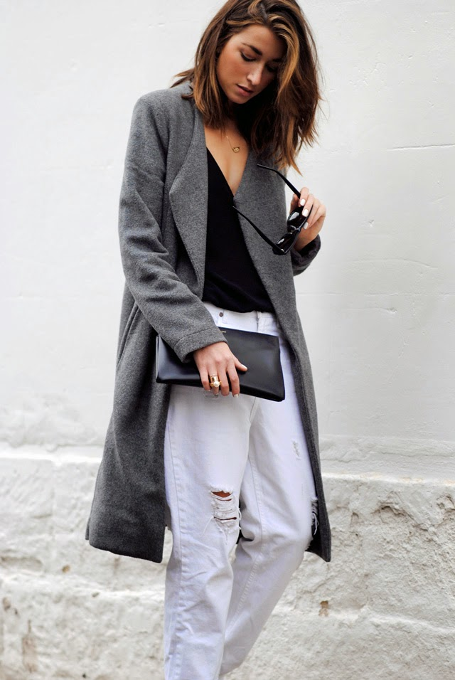 Carmen Hamilton is wearing an oversized grey coat from Life With Bird, black cami from J. Brand, pair of white ripped jeans from ASOS, clutch from Saint Laurent