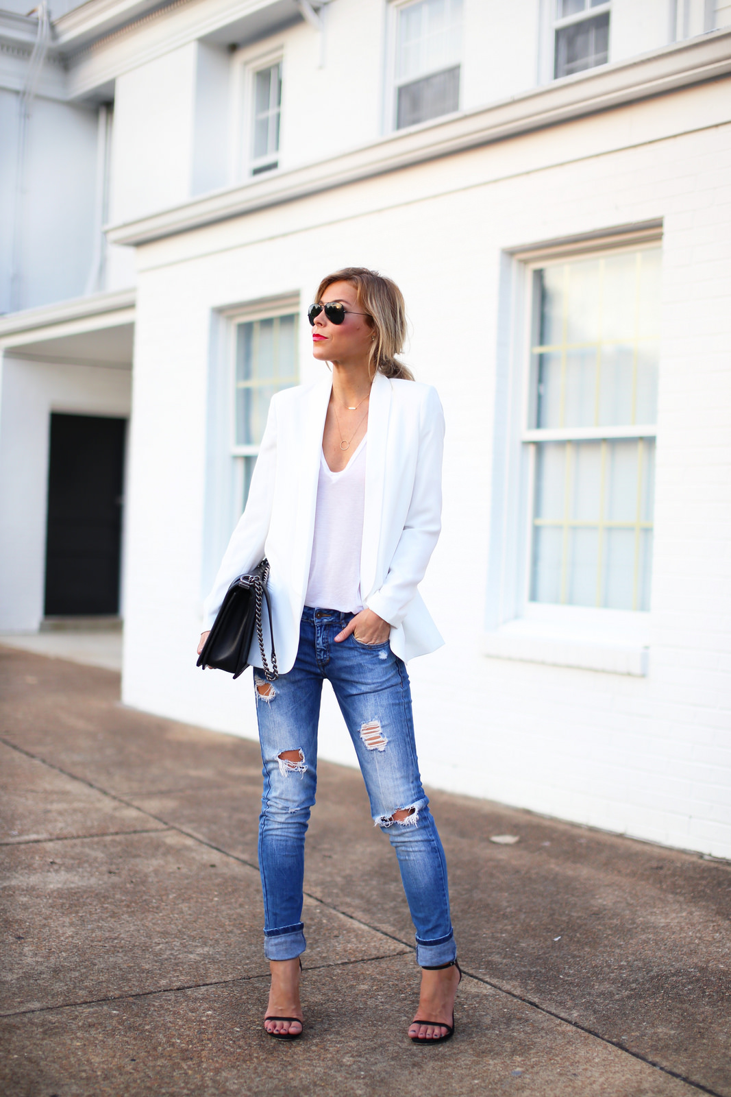 White blazer with black outlines is worn atop black-white striped top tucked in black skinny trousers completed with golden pointed-toe red pumps. White structured blazer looks refined and chic worn atop black top teamed with ripped washed blue boyfriend cuffed jeans and black pumps.
