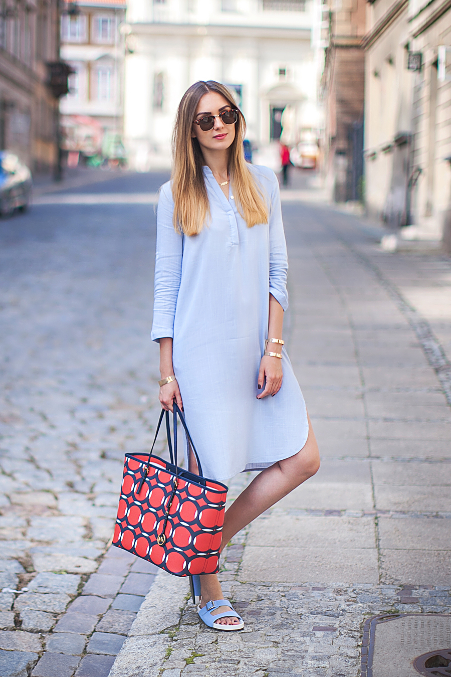 Nika Huk is wearing a light blue shirt dress from ChicNova, matching sliders and sunglasses from ASOS and a bag from Michael Kors