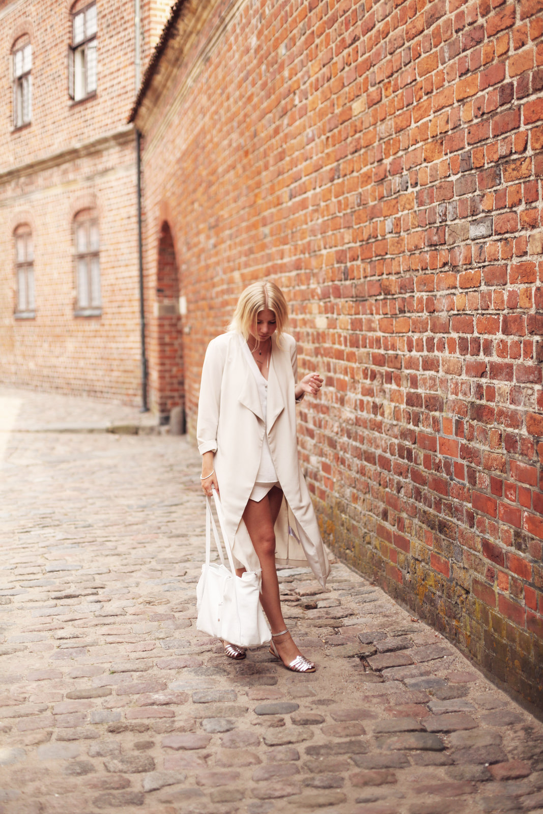 Camilla Ackley is wearing a white trench coat from Vero Moda, top from Mango, skirt and bag from Zara, sandals from Steve Madden