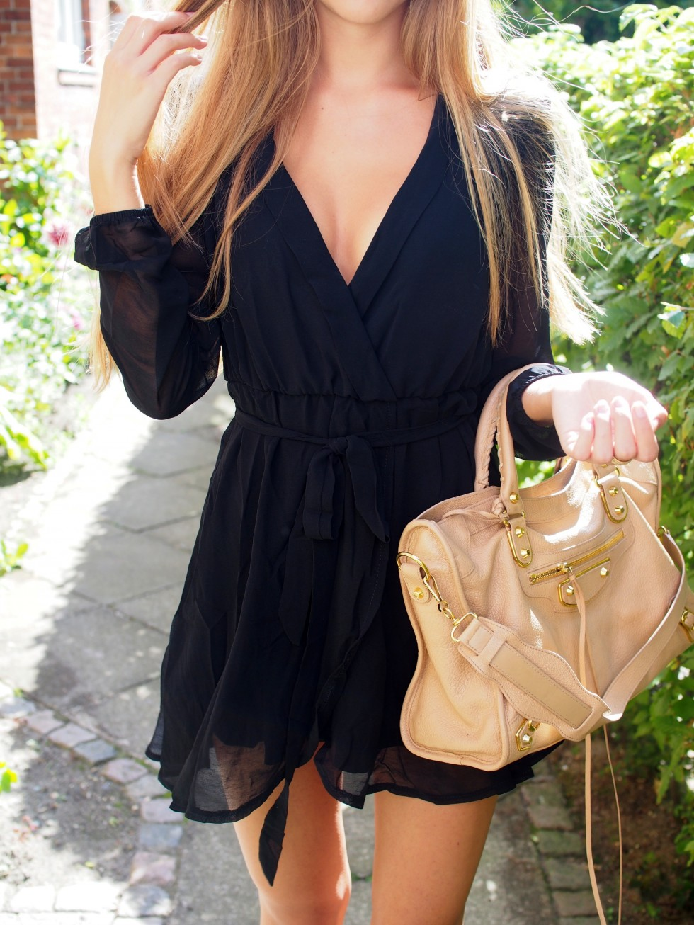 Sandra Willer is wearing a black wrap dress from NLY