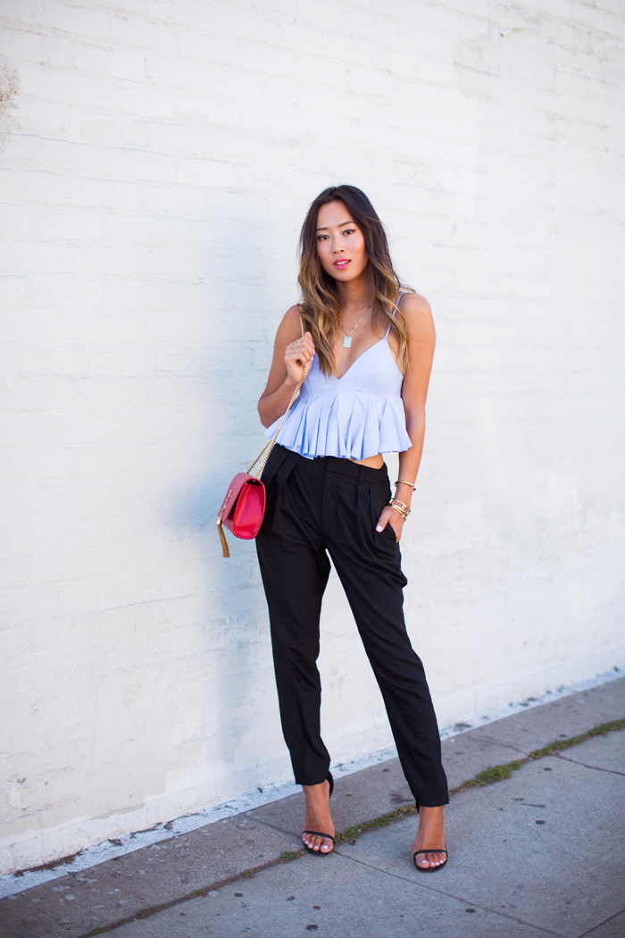 Aimee Song is wearing a light blue pleated crop top from Alexander Wang, pleated trousers from Helmut Lang and tassel bag and shoes from Saint Laurent