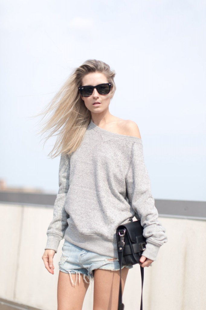 Figtny is wearing a grey sweatshirt from Heather Grey, denim shorts from Aritzia Callahan, the bag is from Proenza Schouler and the sunglasses are from RayBan