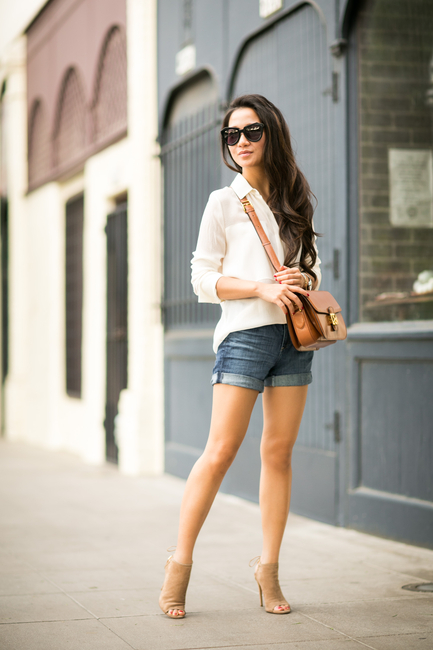 Wendy Nguyen is wearing a cream shirt from Alexander Wang, denim shorts from AG Adriano Goldschmied, bag from Celine, shoes from Aquazzura and sunglasses from Karen Walker