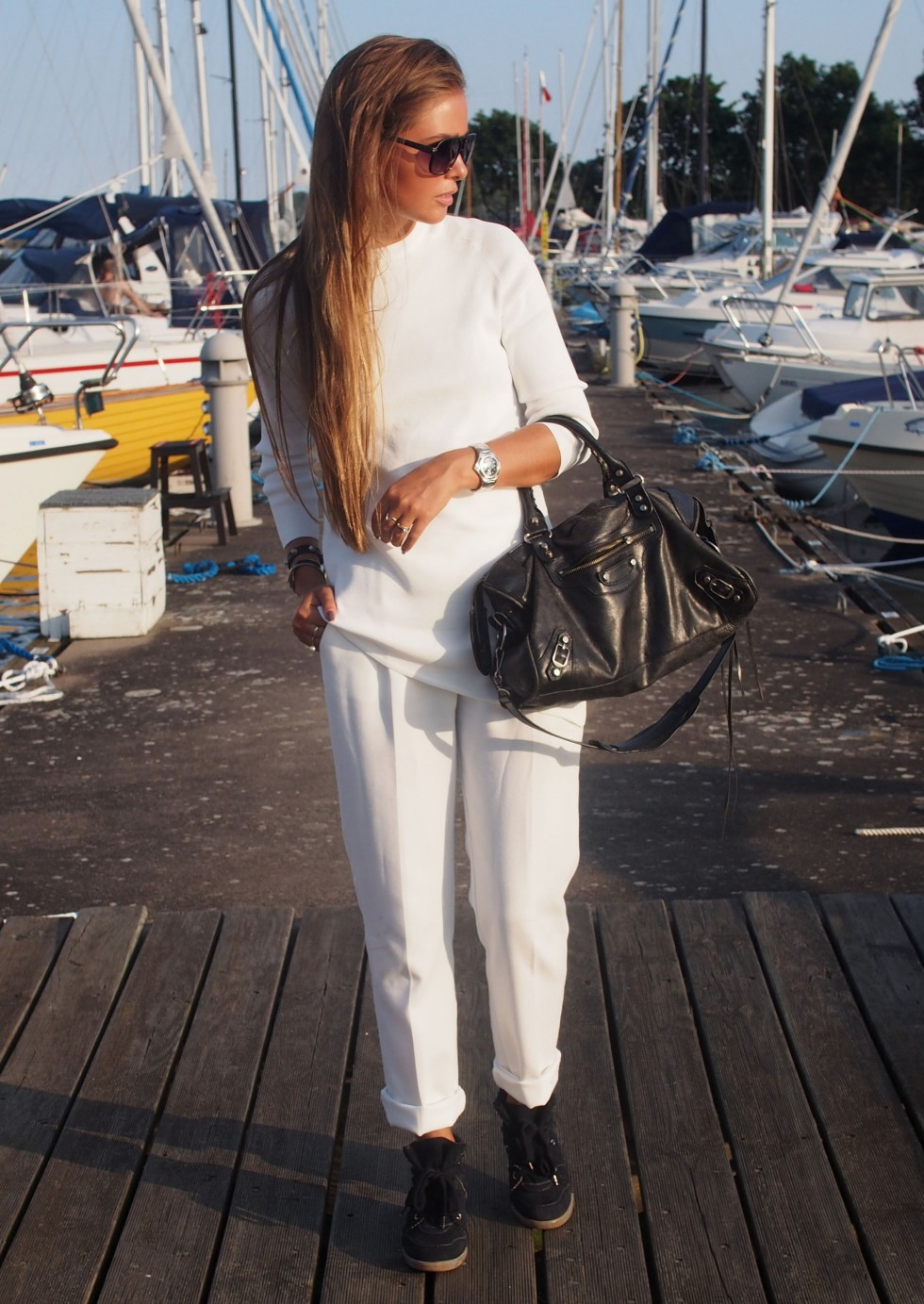Maria Kragman is wearing white on white, trousers from ASOS, top from Zara, sneakers form Isabel Marant and the bag is from Balenciaga