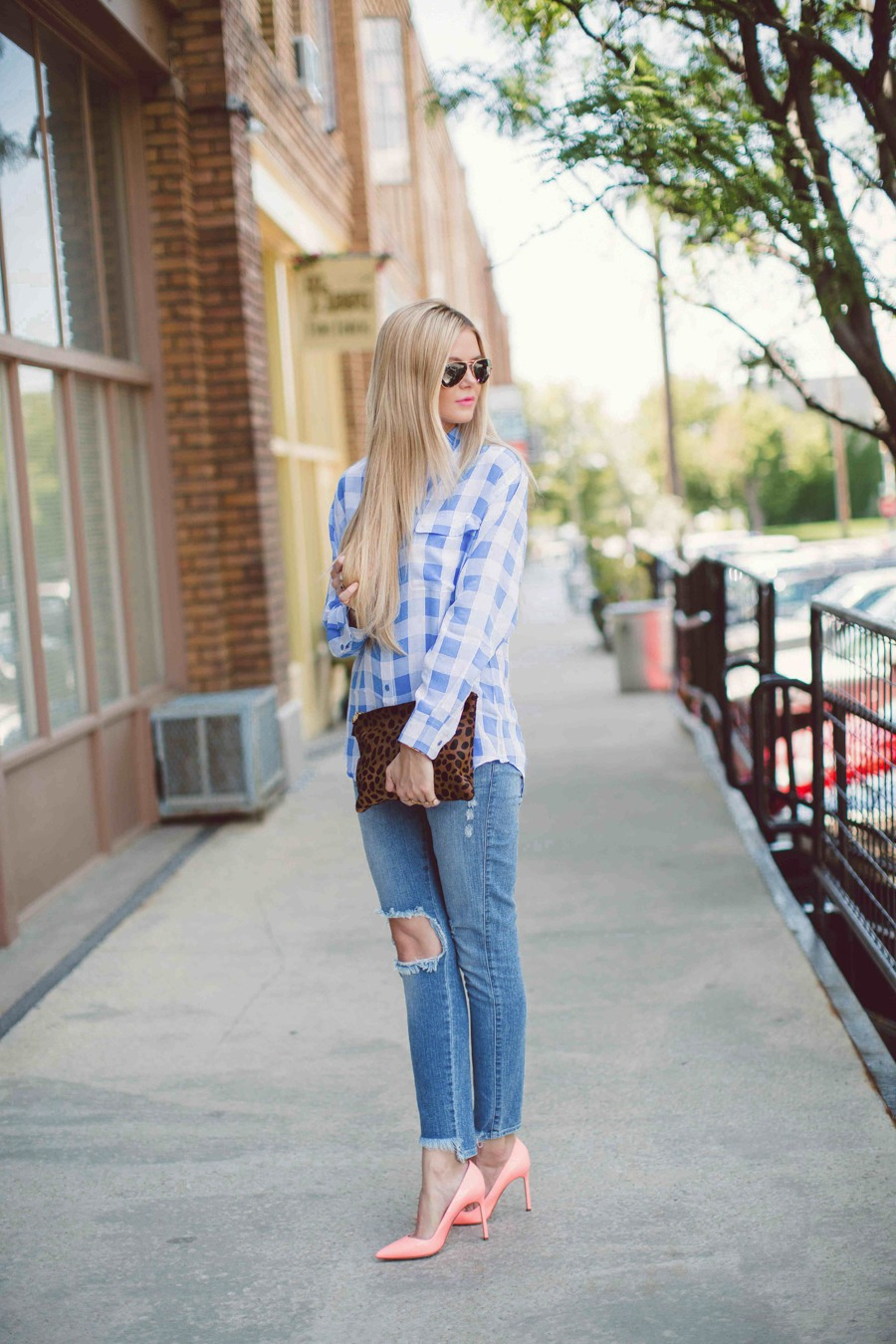 Amber Fillerup Clarke is wearing a blue and white plaid shirt from Equipment, distressed jeans from ShopBop, shoes from Manolo Blahnik and a clutch from Clare Vivier