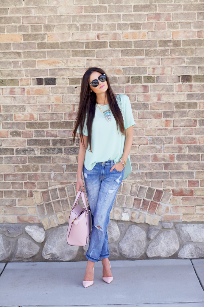 Rachel Parcell is wearing a pastel green top from Topshop, jeans from Current Elliott, shoes from Kurt Geiger, bag from Kate Spade and sunglasses fromKaren Walker
