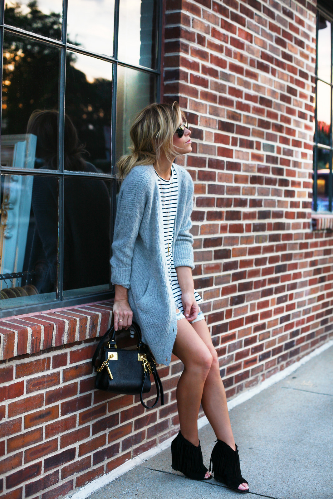 Mary Seng is wearing a grey cardigan from Free People, striped T-shirt and shorts from Necessary Clothing, shoes from Ash and the bag is from Sophie Hulme