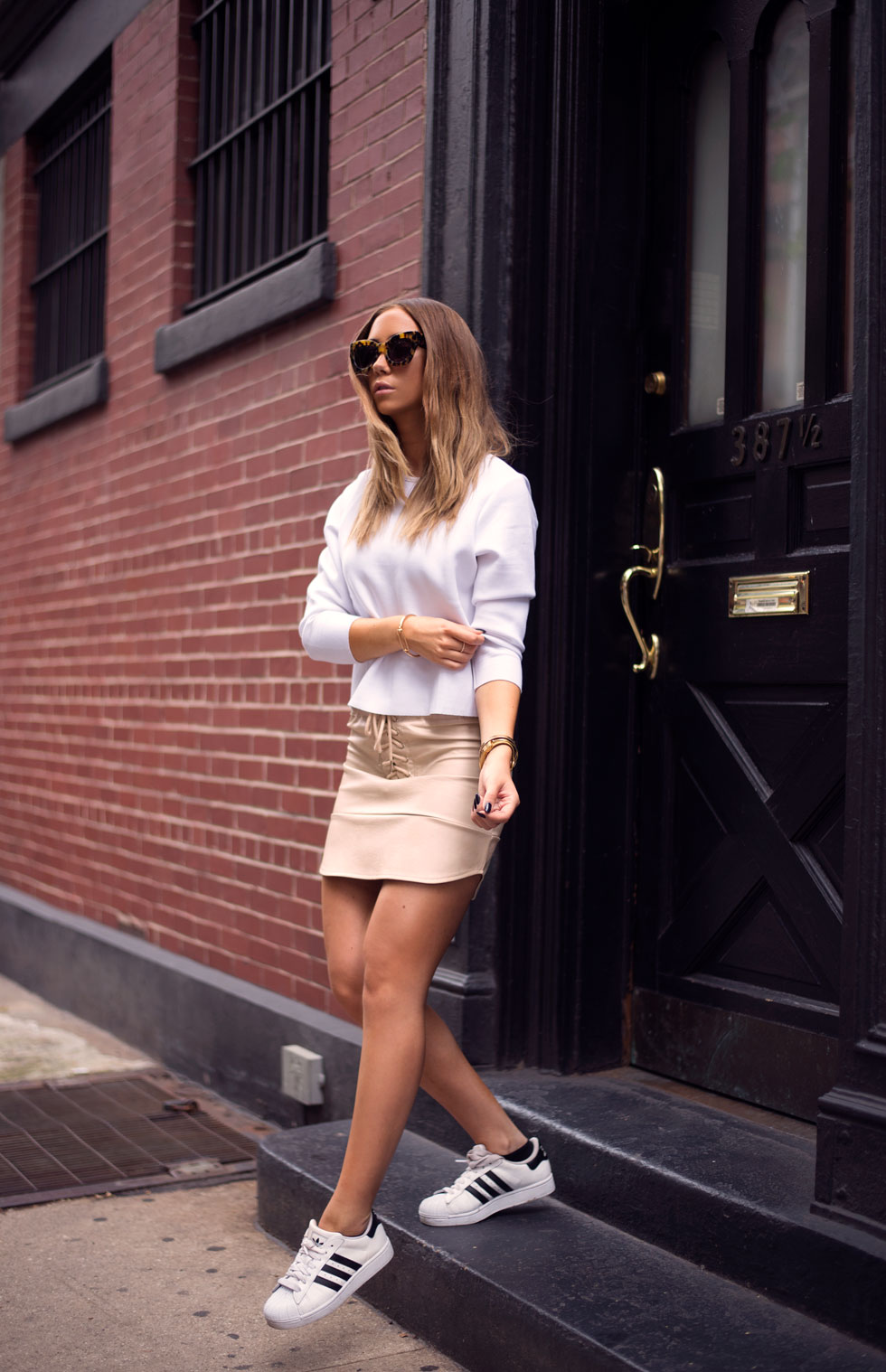Lisa Olsson is wearing a white top from BikBok, nude skirt from Minusey, shoes from Adidas and sunglasses from Karen Walker