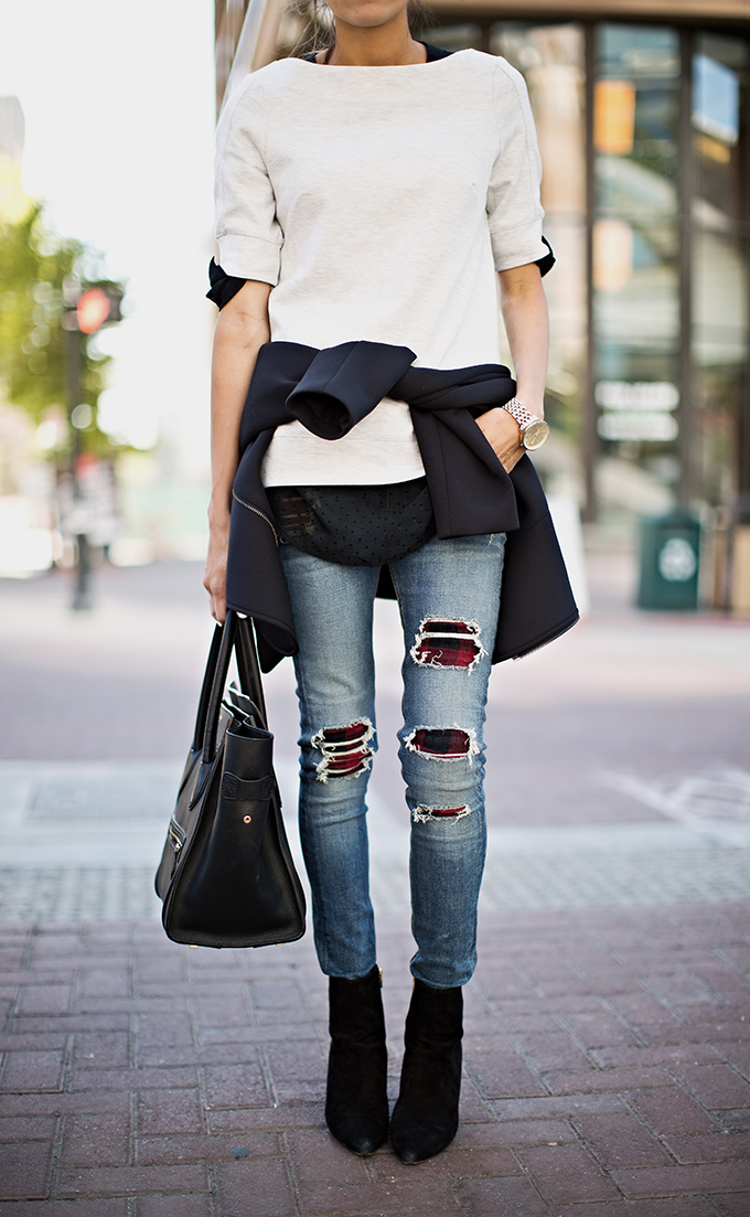 Christine Andrew is wearing a black bomber jacket, jumper from French Connection, plaid distressed jeans from Rag & Bone, black suede boots from Alexander Wang and the bag is from Celine
