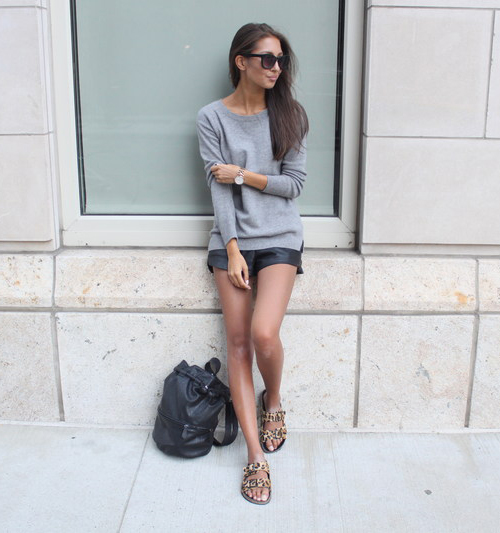 Felicia Akerstrom is wearing a grey crewneck top from Uniqlo, leopard print flip flops from Necessary Clothing, leather shorts from Zara and the bag is from H&M