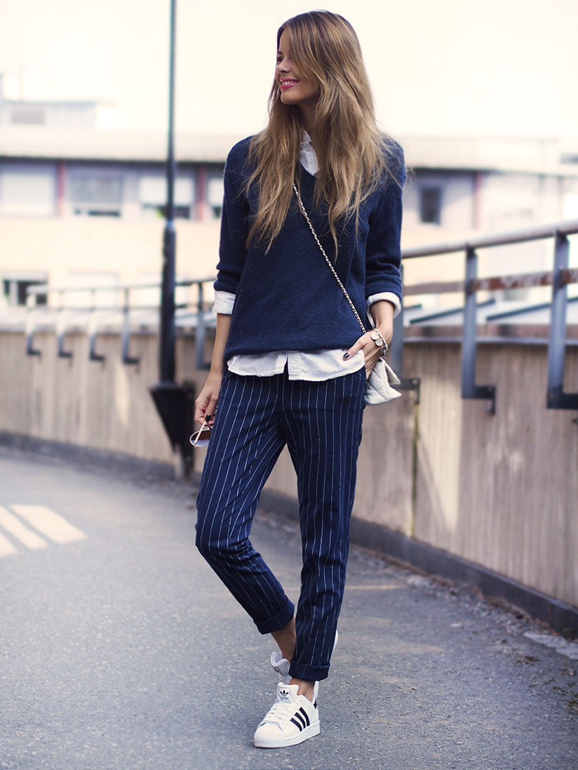 Annette Haga is wearing a sweater and pinstriped trousers from Bik Bok, shirt from Asos, bag from Steve Madden and shoes from Adidas