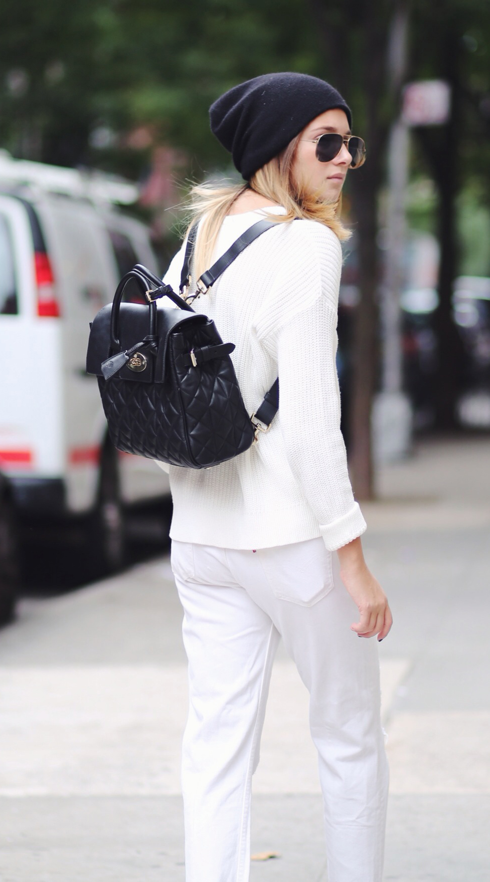 Danielle Bernstein is wearing all white and a black backpack from Mulberry