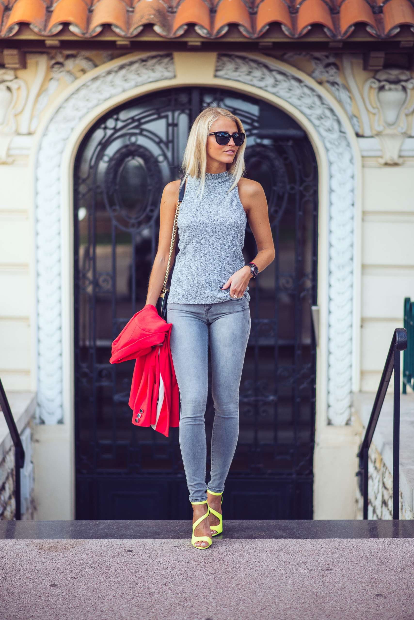 Janni Deler is wearing a grey fitted crop top, red relaxed fit blazer and grey superskinny jeans and yellow asymmetric stilettos all from River Island