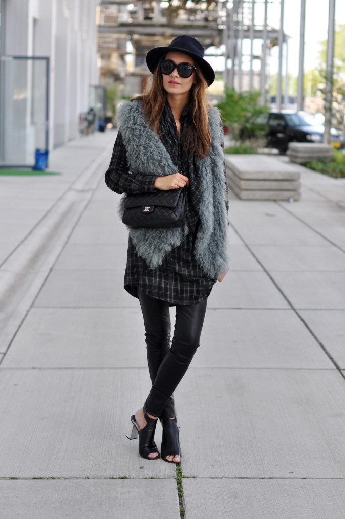 Kelly Elise is wearing a plaid shirt and scarf from Essentiel Belgium, bag from Chanel, shoes from Prada, trousers from DNA and sunglasses from Anine Bing