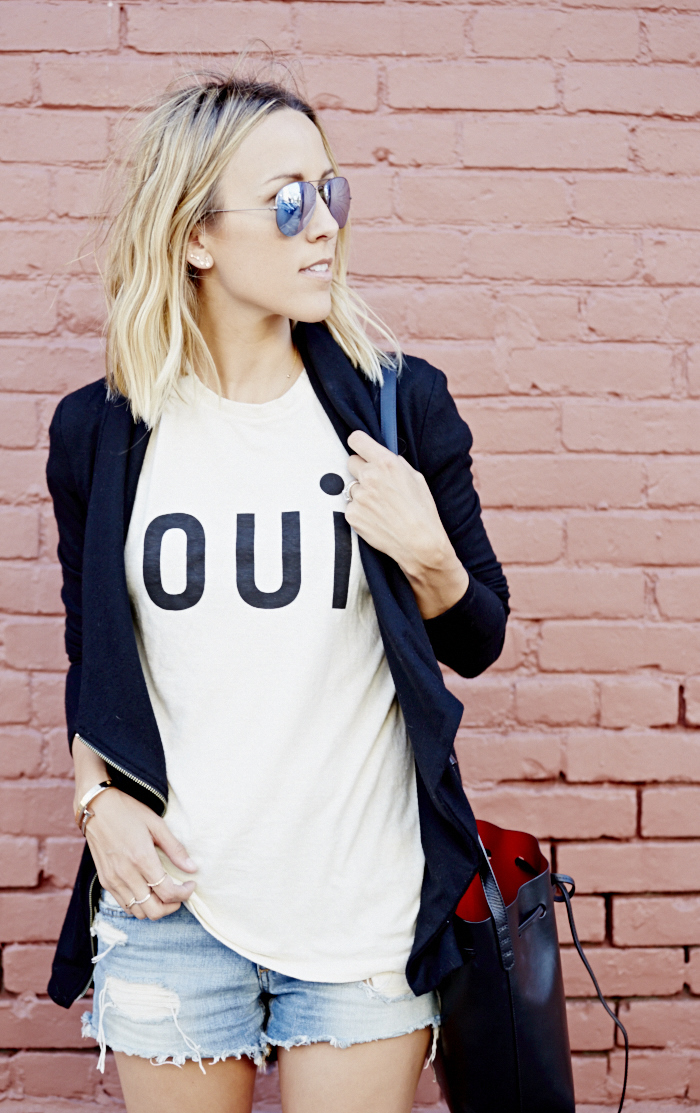 Jacey Duprie is wearing a T-shirt from Clare Vivier, long hooded cardigan from Helmut Lang, bag from Mansur Gavriel and denim shorts from Joe's Jeans