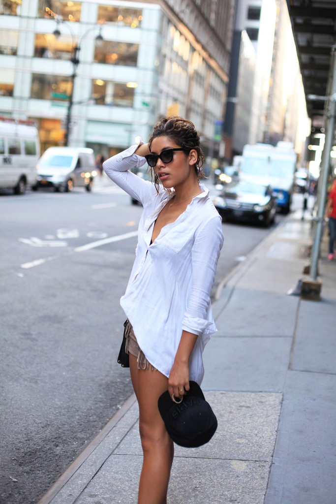 Christina Caradona is wearing a white top and fringed shorts from BCBG