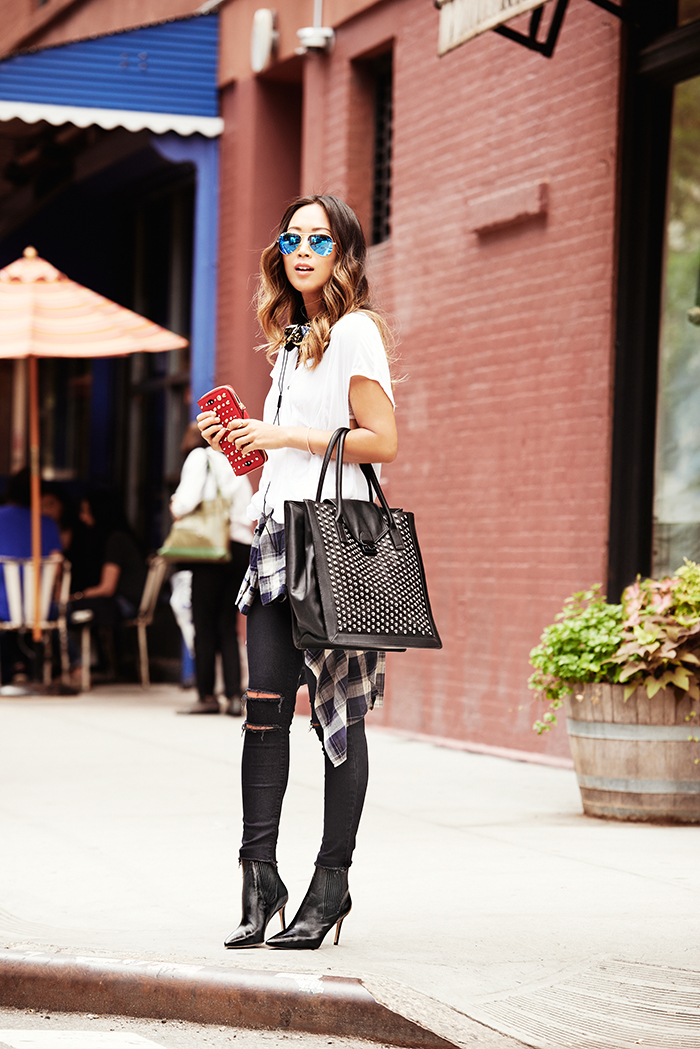 Aimee Song is wearing a white T-shirt, ripped black jeans, chelsea boots, plaid shirt and white print on black bag