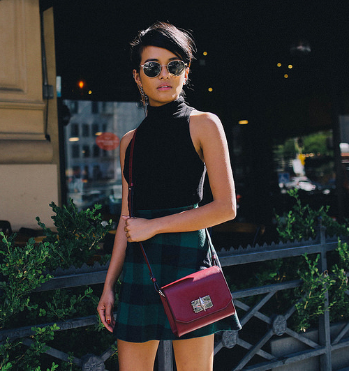 Olivia Lopez is wearing a black knit crop top and a plaid pleated mini skirt from Reformation