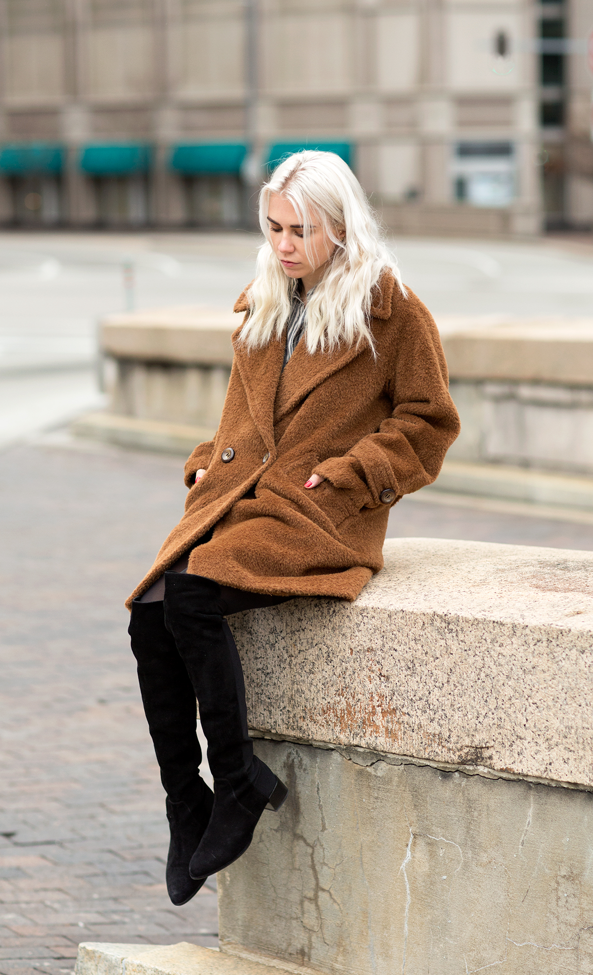 Courtney Trop is wearing a brown double breasted wool and alpaca coat from Trina Turk