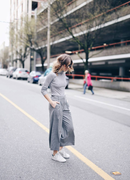 Combine the grey on grey and culottes trends to steal Jill Lansky's awesome and individual style. Consisting of a grey turtleneck, grey culottes, and simple white sneakers, this look is perfect for work and leisure! Brands not specified.