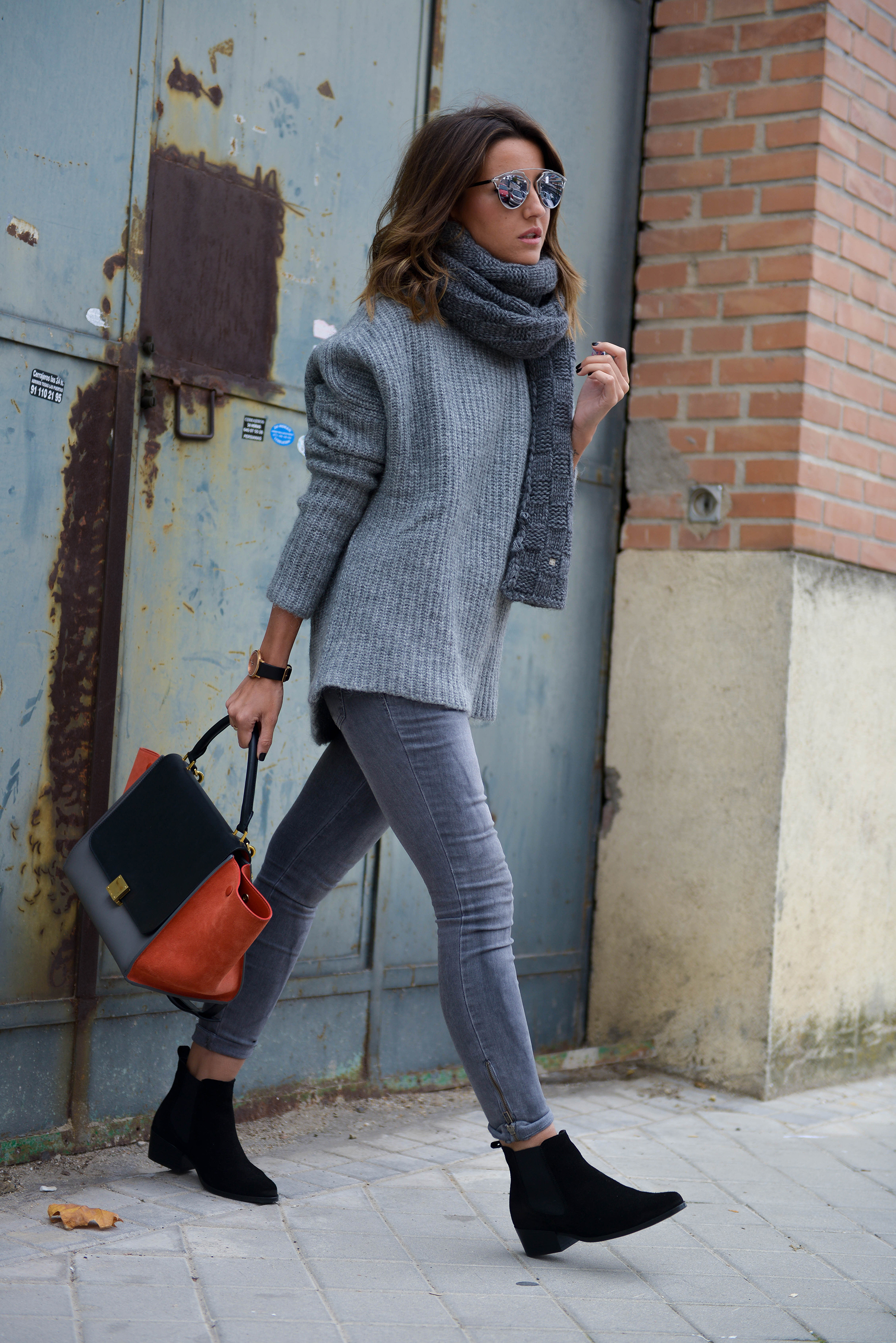 Matching varying tones of grey can really enhance your everyday look. Alexandra Pereira wears a dark scarf with a paler knitted sweater and looks totally ready for work or play. Jeans: Anine Bing, Sweater: Zara, Bag: Celine, Boots: Ulanka.