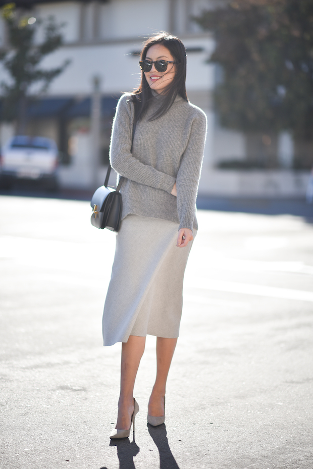 Ann Taylor wears the grey on grey fashion trend in a sweater and matching cashmere skirt; two pieces which go together perfectly for a wonderful winter look. Sweater: Madewell, Skirt: Theory, Pumps: Jimmy Choo.