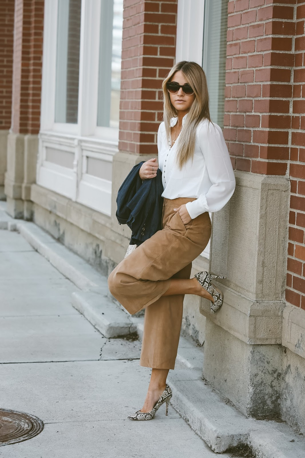 Cara Loren looks stylish in suede in these gorgeous culottes, paired with a simple white blouse and faux snakeskin boots! We love this glamorous look! Outfit: White House Black Market.