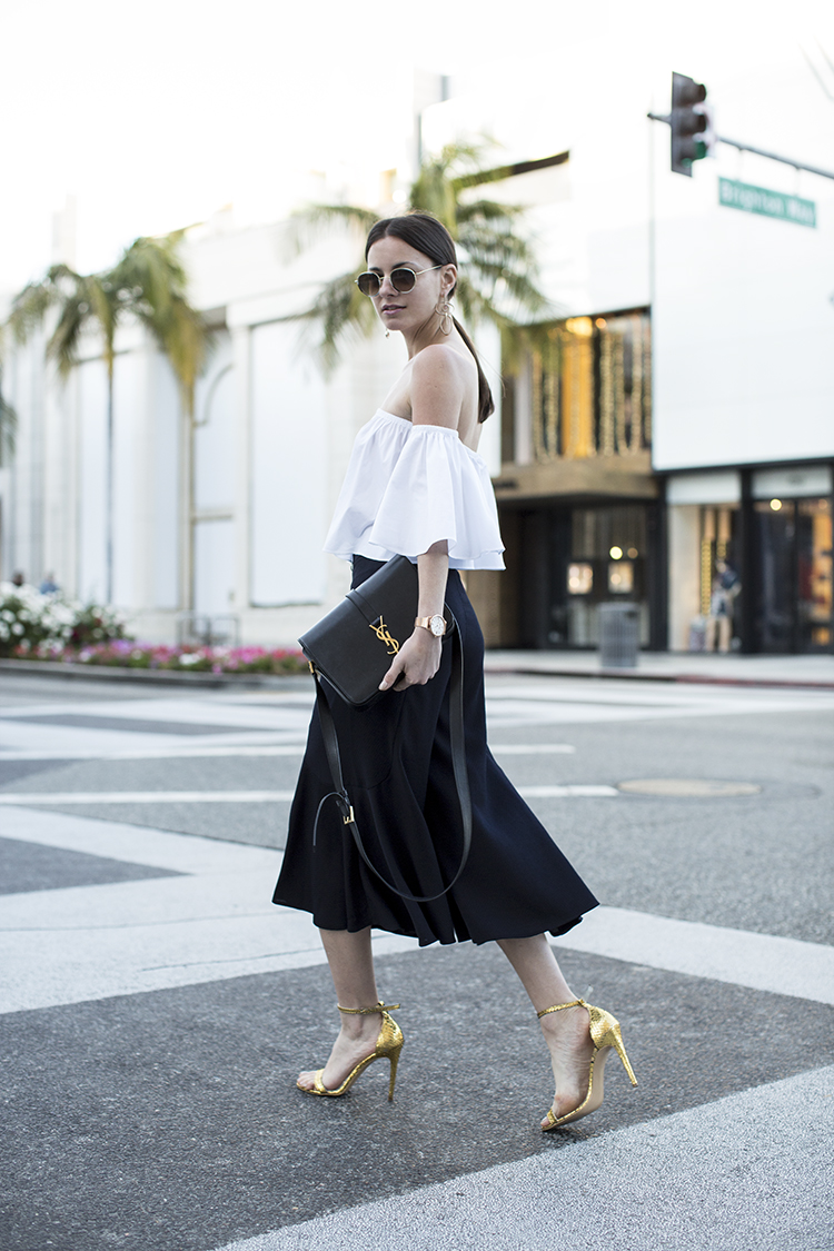 Zina Charkoplia looks utterly elegant in this gorgeous black and white combo, consisting of an off the shoulder bell sleeved blouse and a simple pleated midi skirt. Try wearing this look with a pair of statement heels to steal Zina's aesthetic! Trousers/Top: Zara, Sandals: Smiling Shoes, Bag: Saint Laurent.