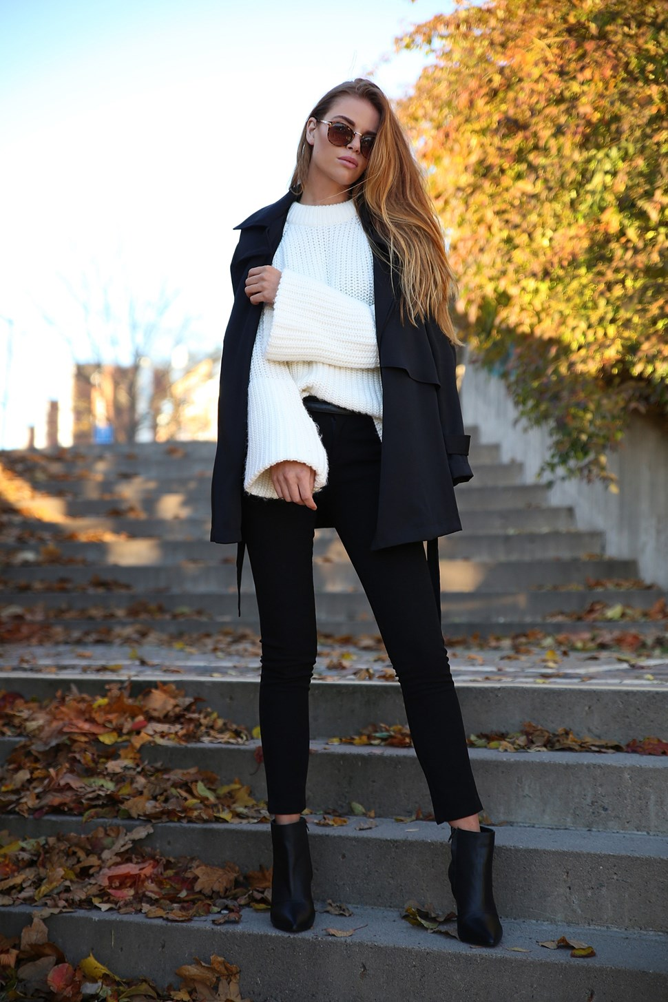 Josefin Ekström rocks monochrome in a white knit sweater with tight black trousers and Chelsea boots. Knit Sweater: Gina Tricot, Trousers: OOTD Store.