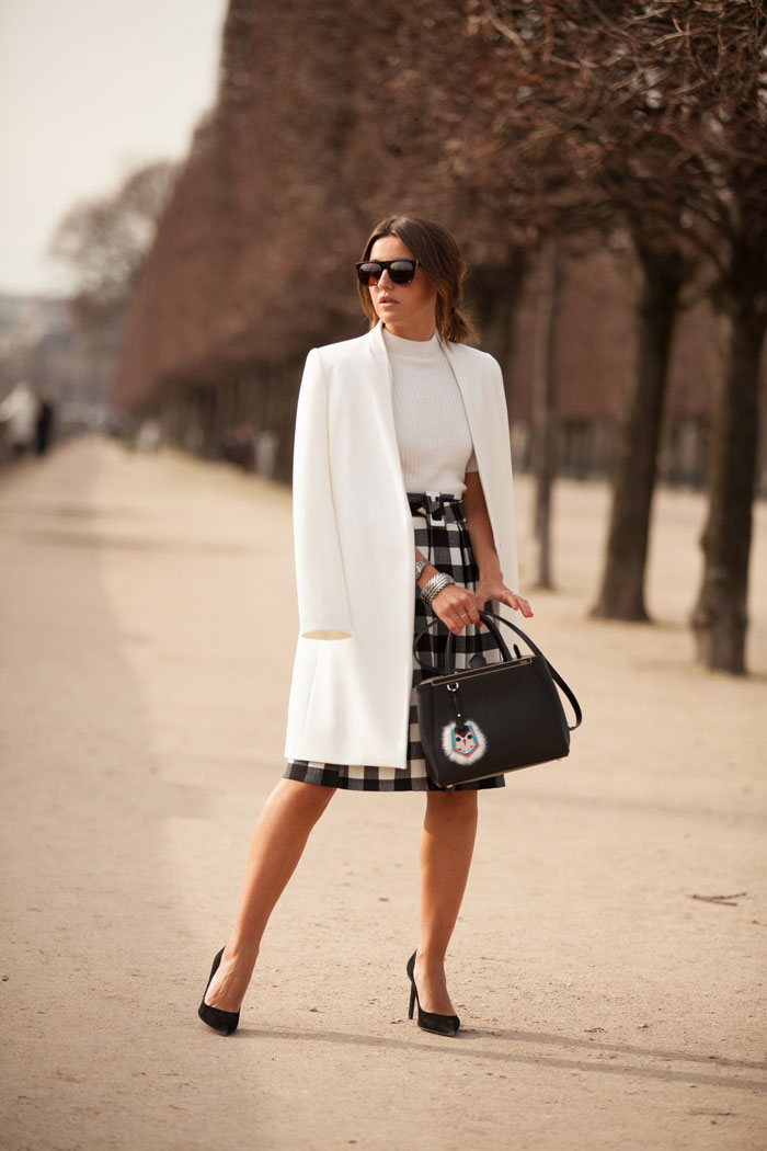 Alexandra Pereira is wearing an all black and white outfit, check skirt from Chicwish, shoes from Yves Saint Laurent, white coat from Zara, white jumper from Monki and the bag is from Fendi