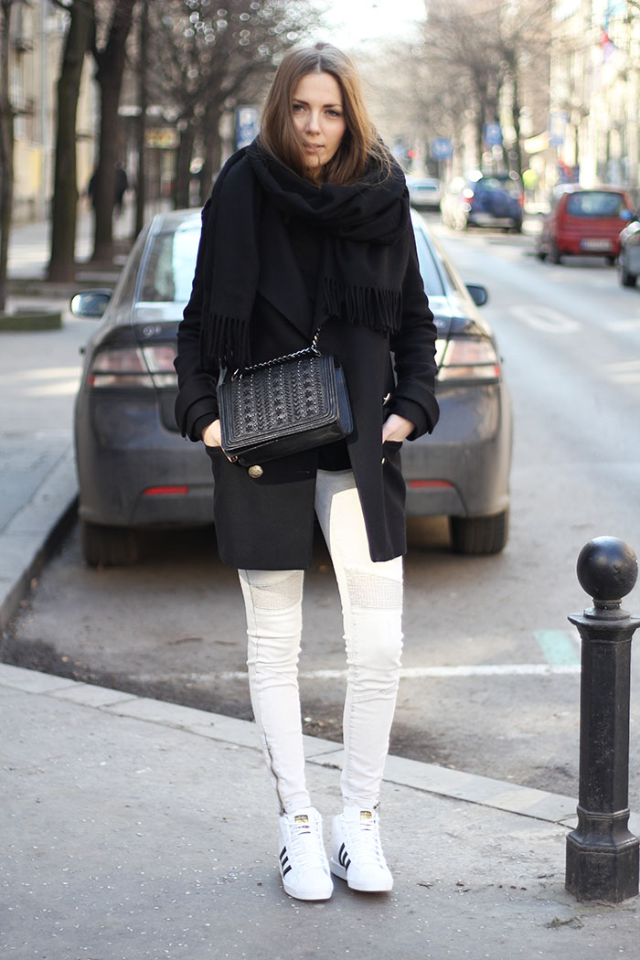 Vanja Milicevic is wearing black and white sneakers from Adidas, white jeans and black coat and bag from Zara, black and white scarf from Acne Studios