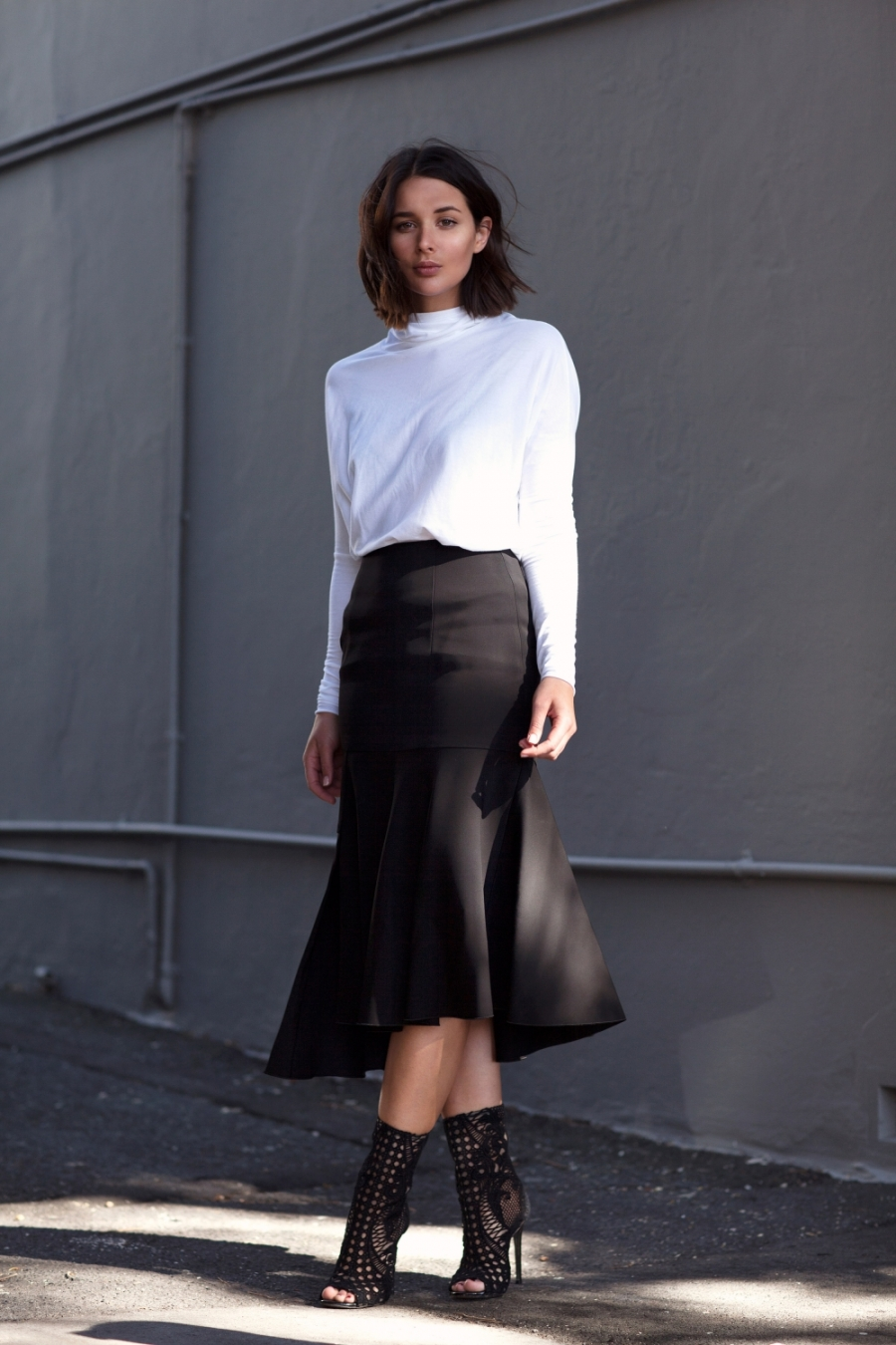 Sara Donaldson in a simple black skirt and shoes and a white top Skirt: Josh Goot, Top: Country Road, Shoes: Balmain