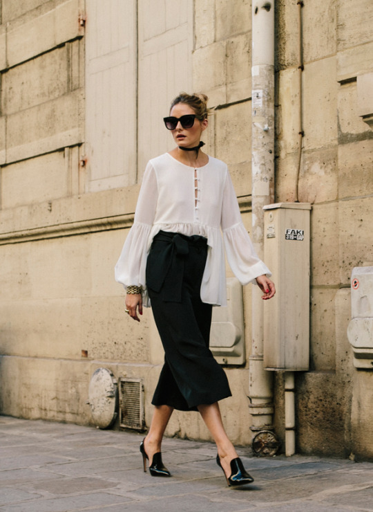Olivia Palermo is strikingly contrasting in this monochrome outfit consisting of a white bell sleeved blouse, black culottes and a pair of asymmetrical patent black heels. Throw on some shades to get all the glamour Olivia has achieved! Heels: Gianvito Rossi.