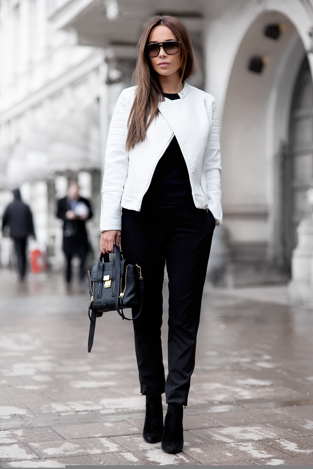Black and White Outfit Ideas: Johanna Olsson is wearing a white leather jacket with black trousers ankle boots