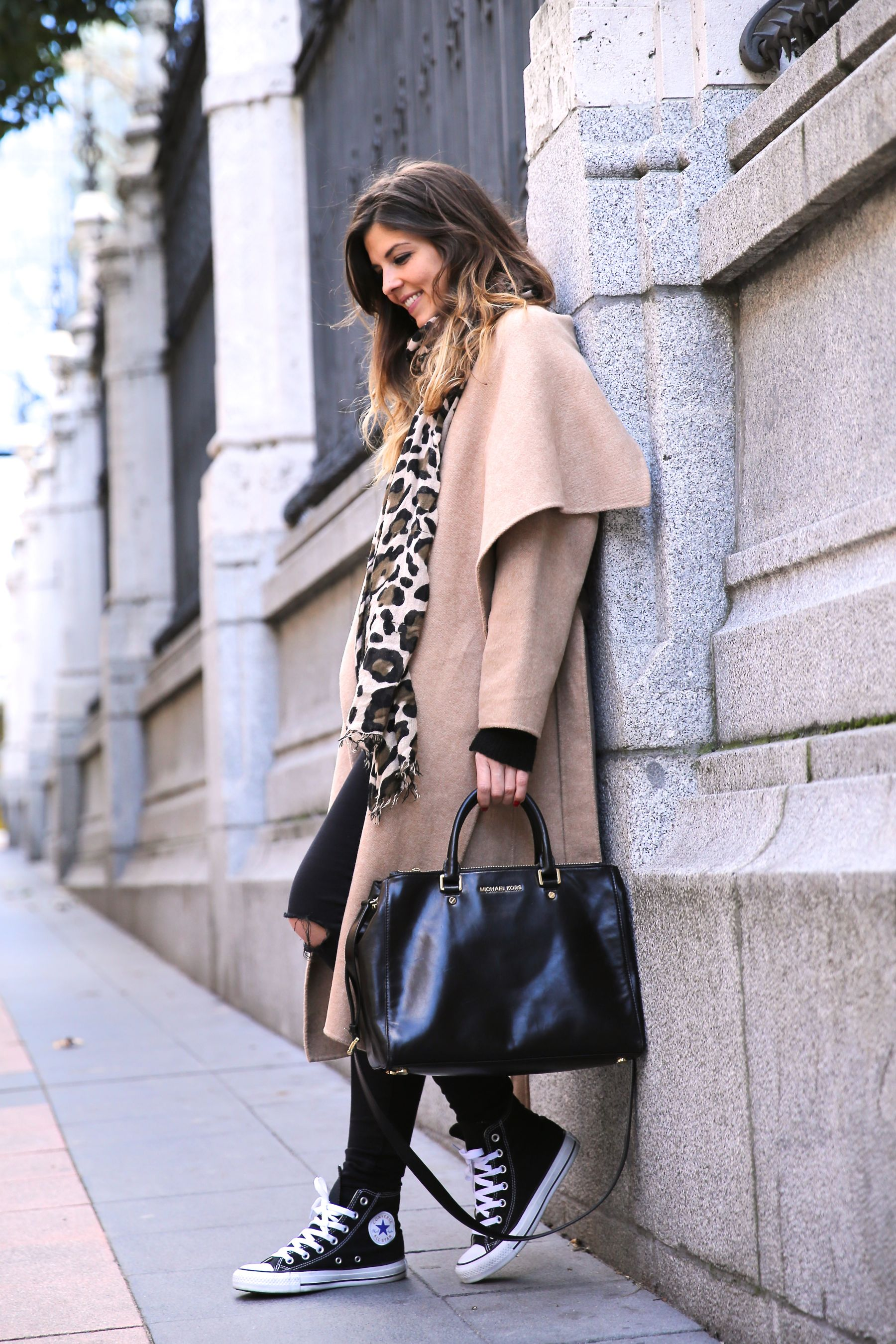 Natalia Cabezas is wearing a camel coat from Zara, black jeans from Asos, leopard print scarf, bag from Michael Kors and black Converse