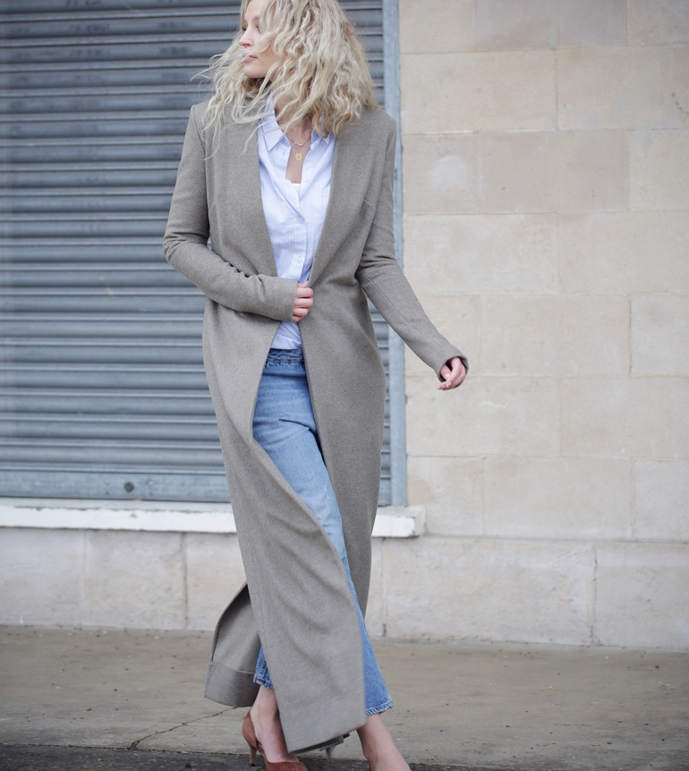 Street Style Fashion: Anouk Yve is wearing a grey long coat from Anouk Yve & Emily King, pale blue shirt from & Other Stories, jeans from Acne Studios, and the brown shoes are from Ganni