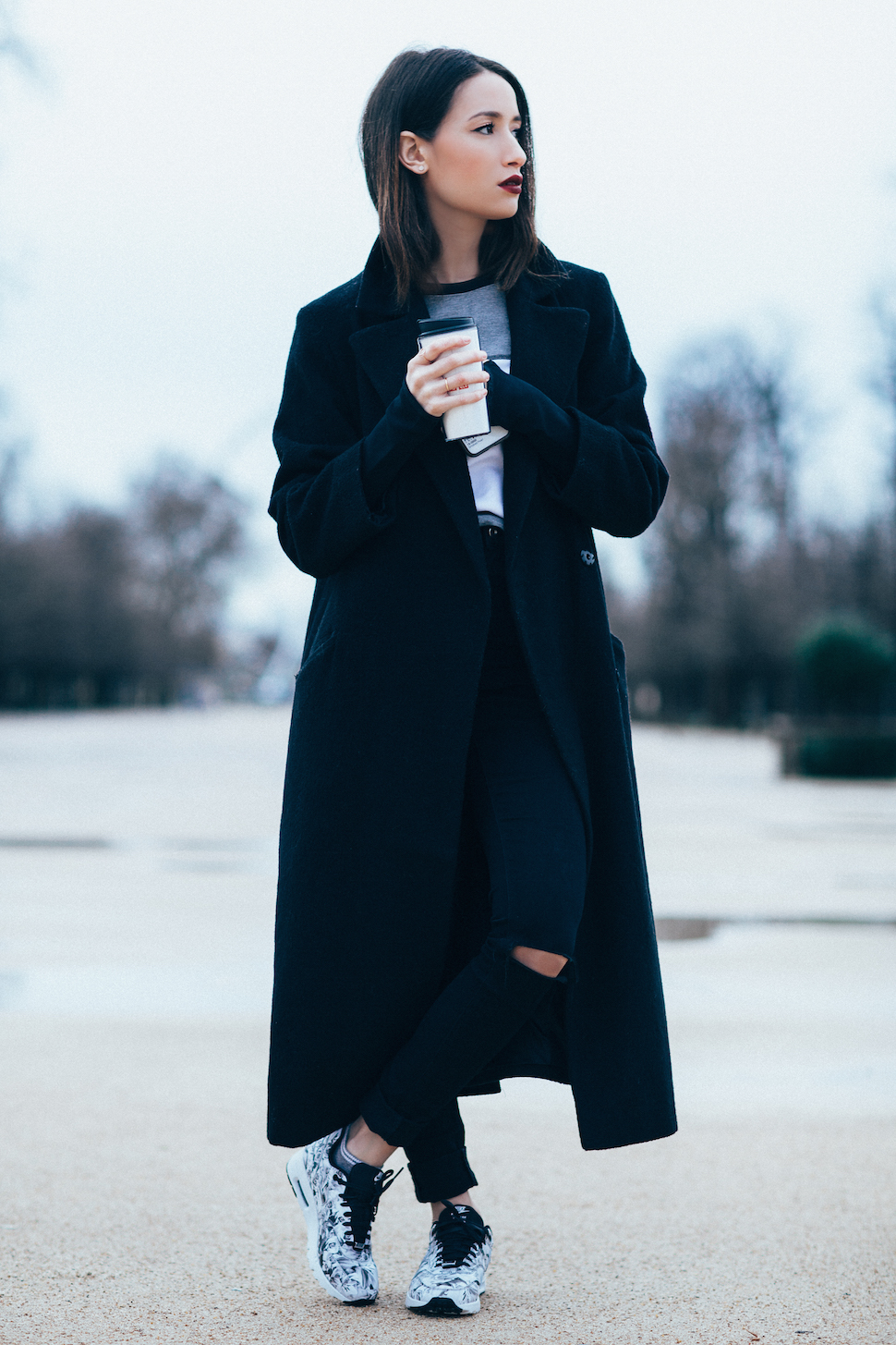 Just The Design: Alexandra Guerain is wearing a black trench coat with black skinny jeans and Nike sneakers
