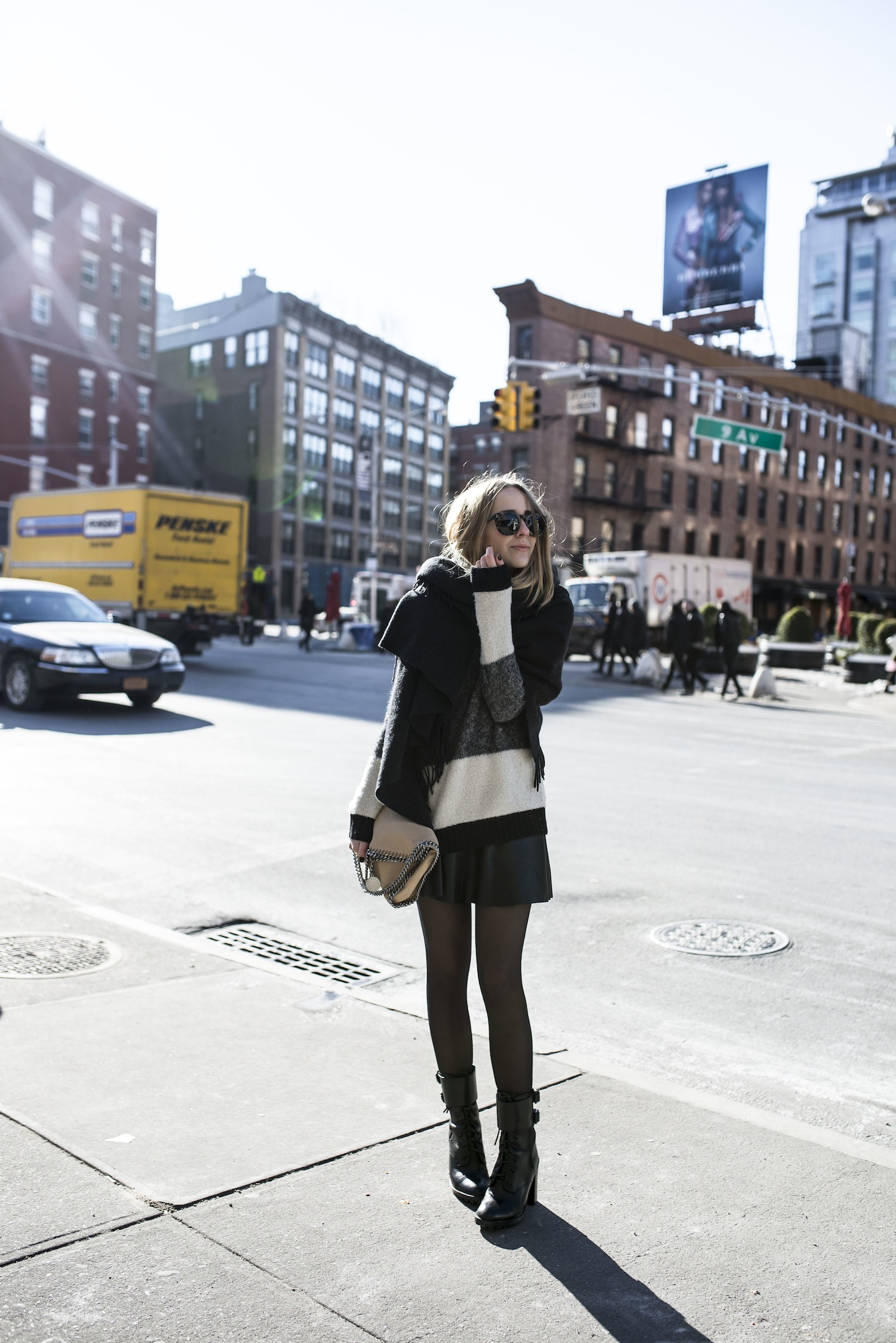Just The Design: Tiphaine is wearing a striped Blake LDN sweater with a black leather Tommy Hilfiger mini skirt and Tory Burch boots