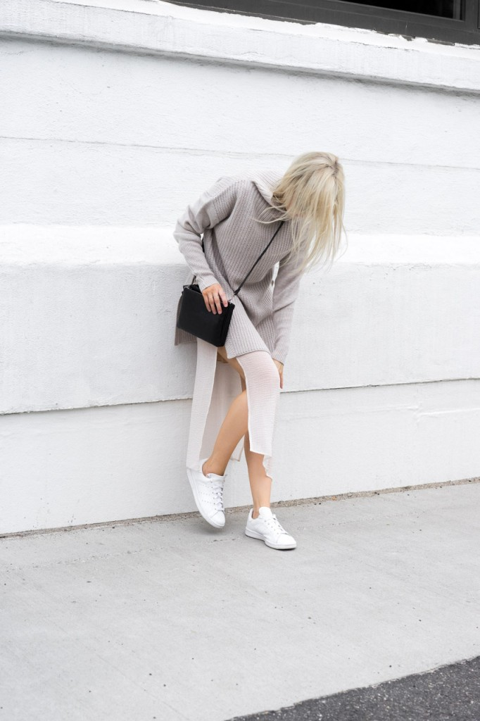 Figtny wears the high slit trend with casual sneakers and a turtle neck pullover. Knit/Skirt: Aritzia.