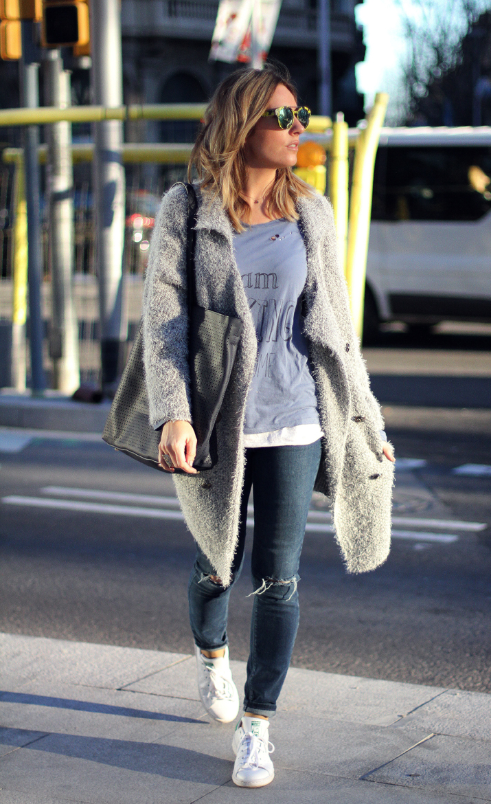 Monica Sors is wearing a grey oversized cardigan with a pair of Tejanos ripped jeans and Stan Smith