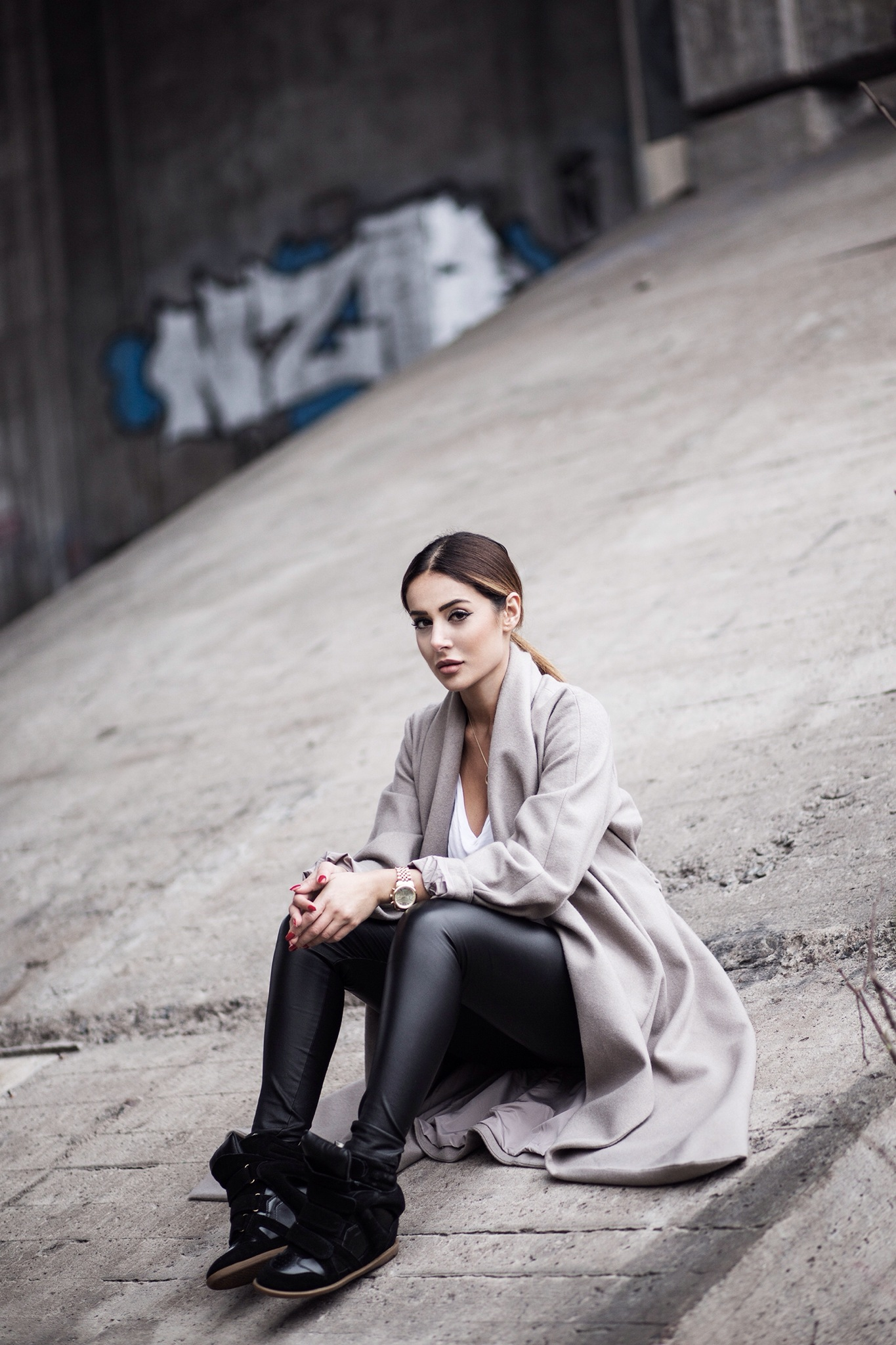 Sharareh Sophia Hosseini is wearing black leather trousers from River Island, white T-shirt- from Gina tricot, grey coat from Weekday and the shoes from Isabel Marant