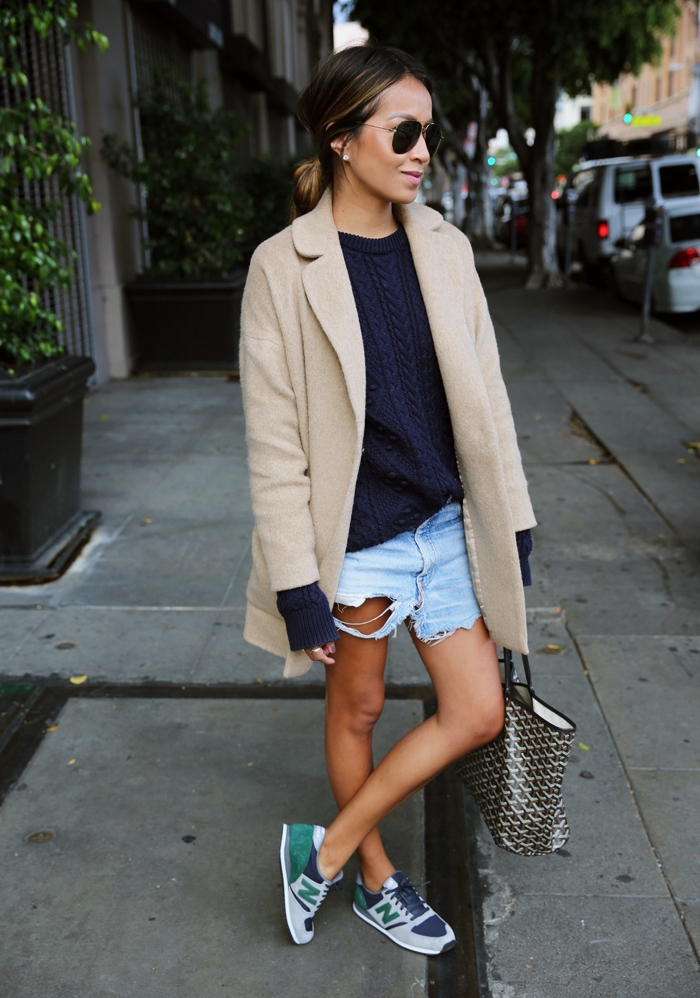 Julie Sarinana is wearing a tan wool cocoon coat from Armani Exchange, blue heavy knit blue sweater from Zara, vintage denim shorts from Levi's and the sneakers are from New Balance