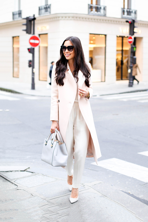 Via Just The Design: Kat Tanita is wearing a creme Club Monaco coat with Phillip Lim trousers and a pastel Victoria Beckham handbag