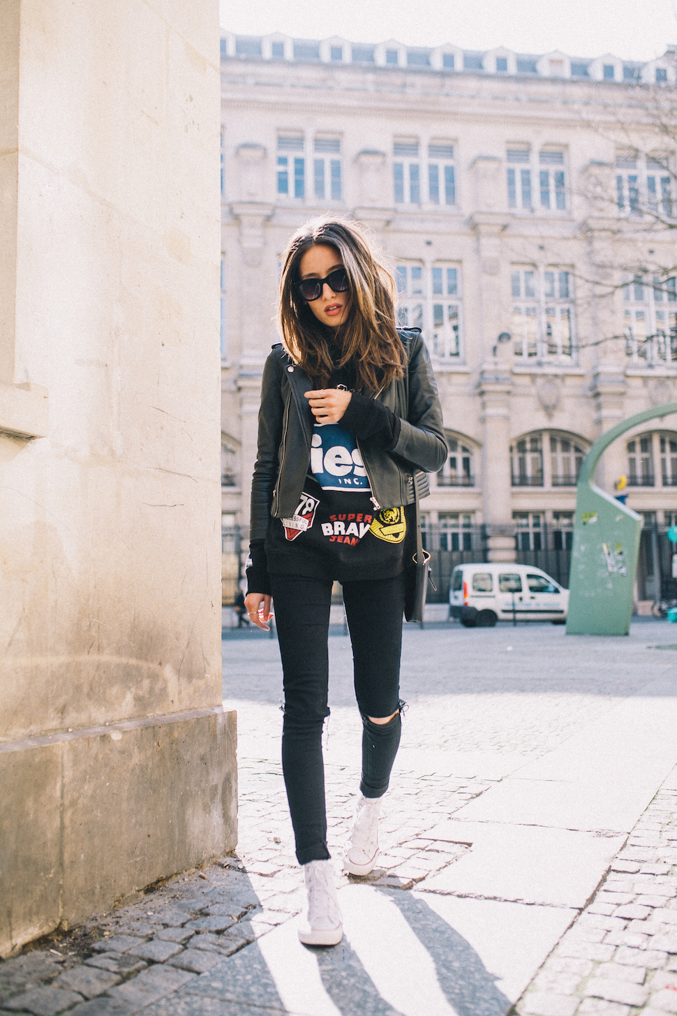 Alexandra Guerain is wearing a black graphic tee with a leather biker jacket, skinny jeans and white Converse sneakers
