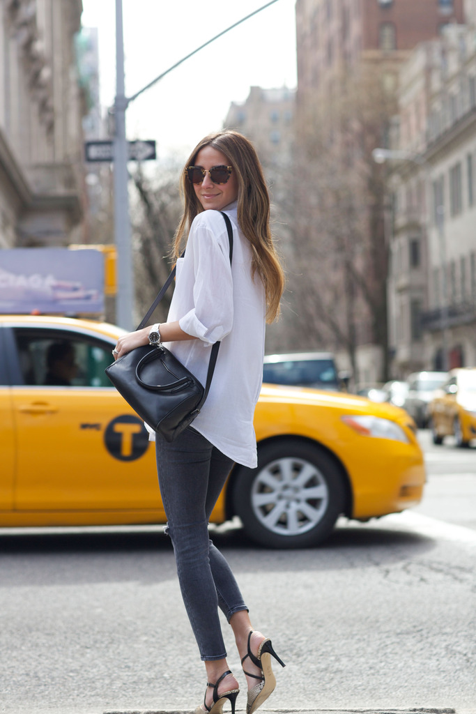 Arielle Nachami is wearing a Elizabeth and James white shirt with a pair of dark grey J Brand skinny jeans, M.Gemi heels and a Reece Hudson black sidebag