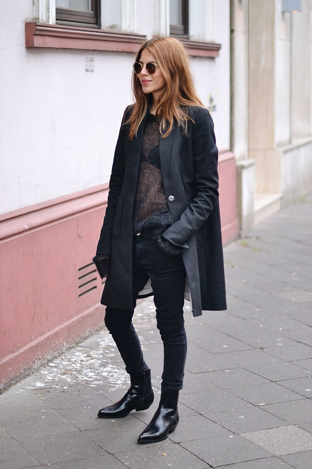 All Black Edgy Outfits: Maja Wyh is wearing a Dorothee Schumacher mac coat and sweater, Sandro skinny jeans and Saint Laurent booties